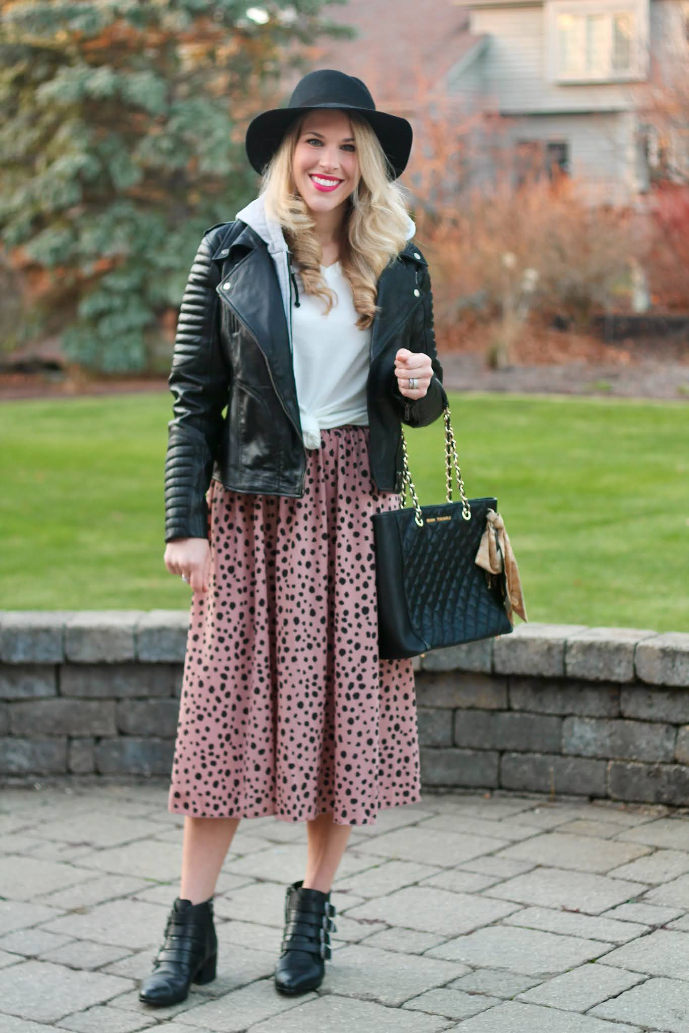 black hooded moto jacket, leopard midi skirt, black quilted tote, black buckle booties, black fedora, casual winter skirt outfit