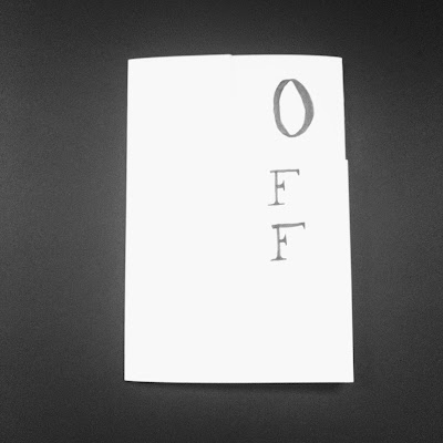 A bird's eye view of the On/Off artist book. The word Off is drawn vertical towards the top right of the book.