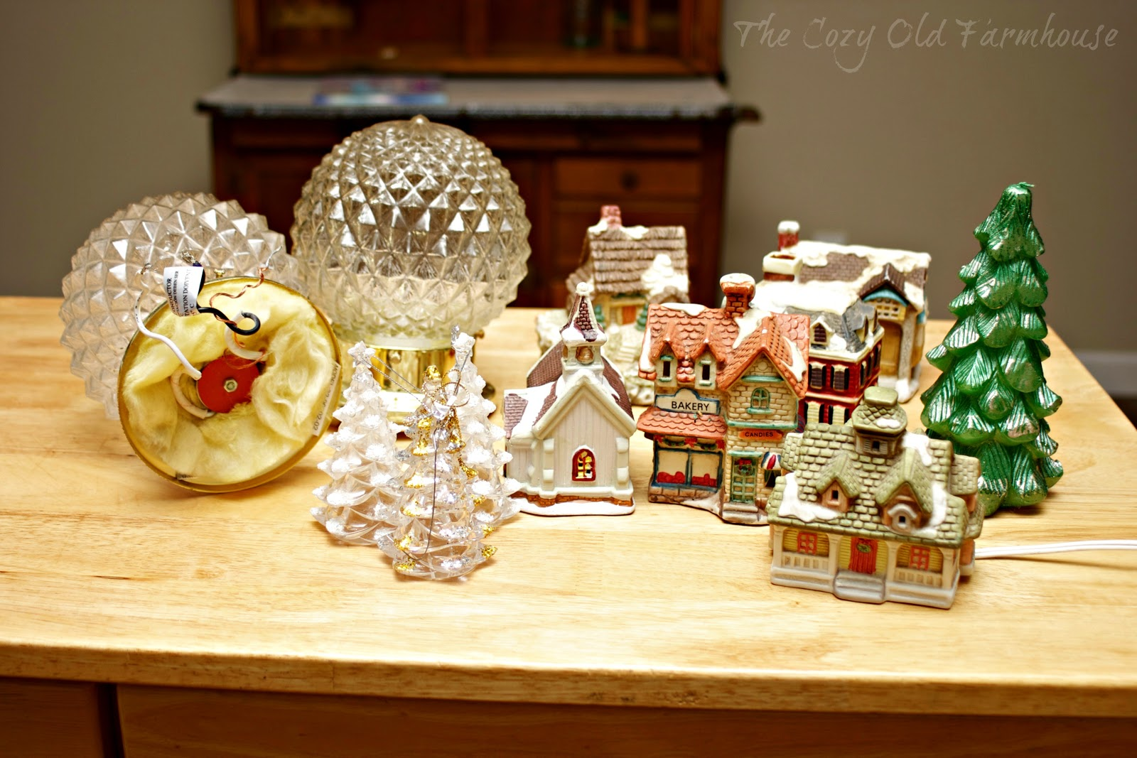 christmas village pieces from thrift stores and yard sales a candle shaped like a tree a couple of christmas ornaments and some leftover light