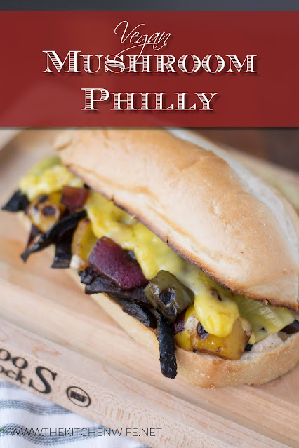 The mushroom philly sandwich, on a small cutting board with chips behind it.