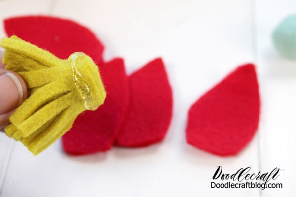 Felt Flower #2: Begin by cutting a strip of yellow felt between 1/2 and one inch wide. Then cut a row of fringe down one edge of the felt. Then add a little hot glue and roll up the entire strip in a spiral, making a fringy center.   Then cut petals out of red felt to place around the yellow center.
