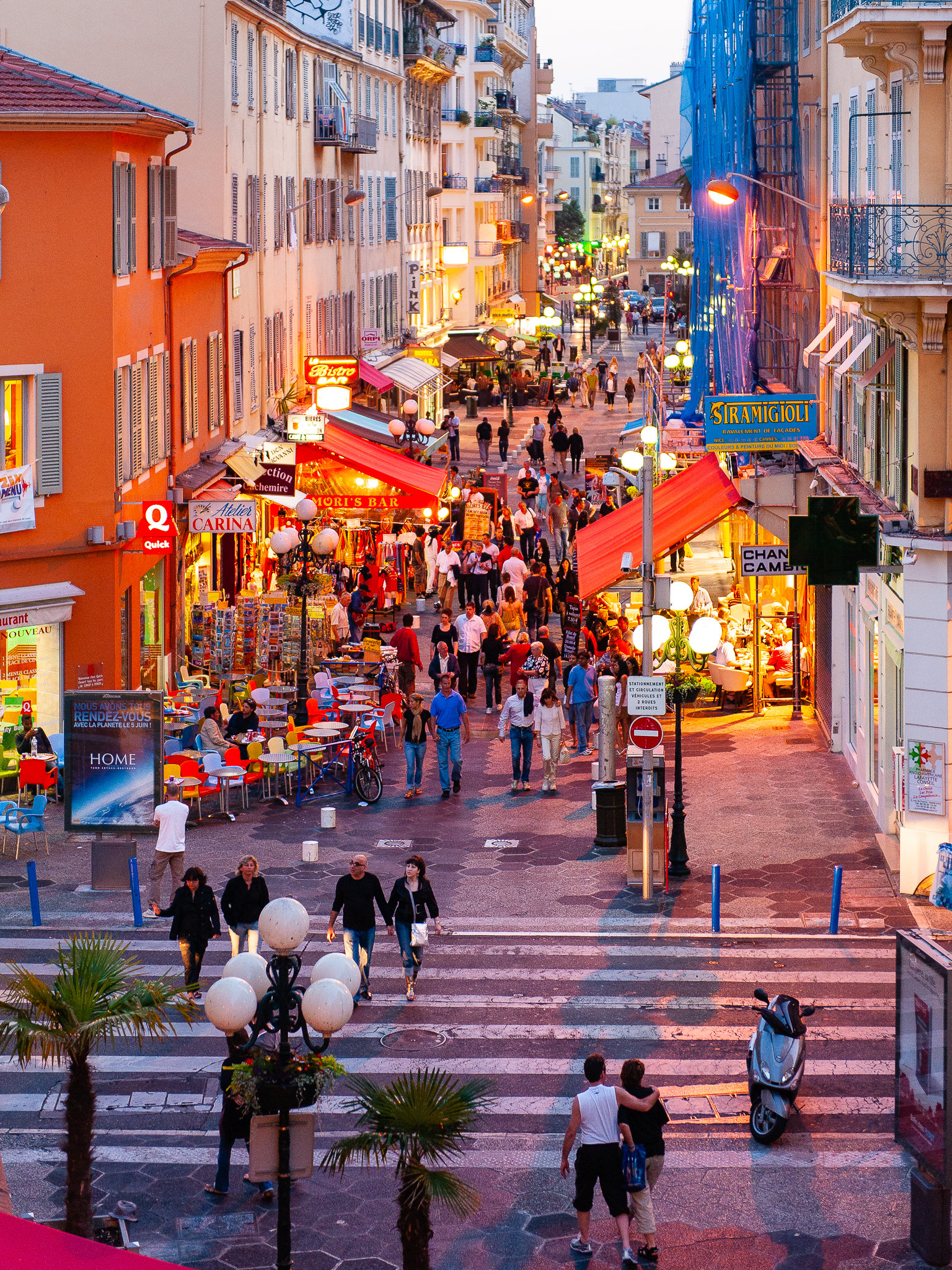 a photo of people walking the streets of nice france on a summer evening