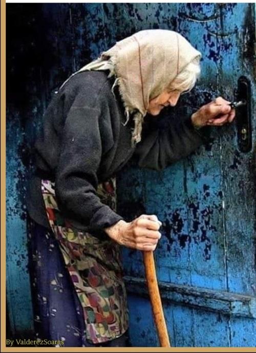 Uma senhorinha de idade avançada caminha lentamente com sua bengala em direção a porta.