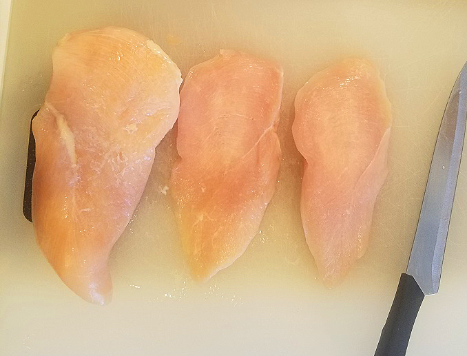these are chicken breast on a white cutting board and knife for chicken fried chicken recipe