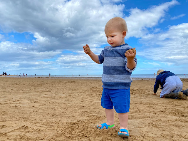 A one year old standing on a sandy beach with his hands full of sand