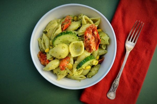 A bowl of pasta salad with sundried tomatoes, cucumber and sweetcorn