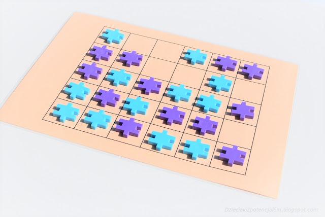 na zdjęciu plansza z polami 5x6, na niej leży w przypadkowym ułożeniu dwanaście pionów w kolorze fioletowym i dwanaście w kolorze niebieskim, za piony posłużyły kocki meli