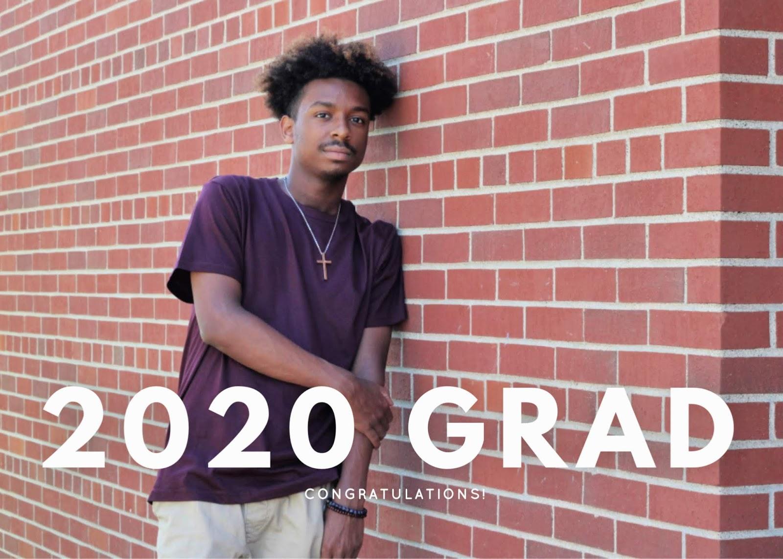 a 2020 high school graduate standing by a brick wall