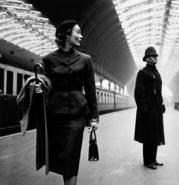 """Victoria Station, London"". Fashion model (identified as Lisa Fonssagrives with English bobby on platform at London's Victoria Station. Photograph by Toni Frissell (one of the most celebrated female photographers of the 20th Century), published by Harper's Bazaar in 1951. Part of a collection gifted to the Library of Congress by Frissell. Very poor scan of a very beautiful picture. I tried my best to bring out the contrasts and remove the various artifacts, but I wish they'd clean it up and scan it again. Note, the location of this picture has been mistaken by United States Library of Congress the actual location is Paddington station."