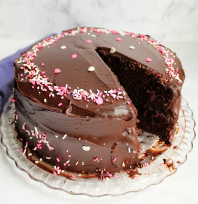 layered chocolate cake with shiny chocolate frosting and sprinkles