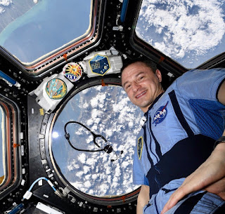 Drew Morgan aboard the ISS with a view of Earth in the background