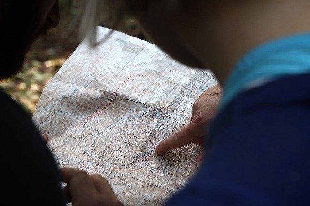tangan pria yang sedang menunjuk pada sebuah peta