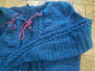 A knit cardigan in dark blue fingering-weight wool, lying flat.  One sleeve is sewn into the armhole and is folded over the body.