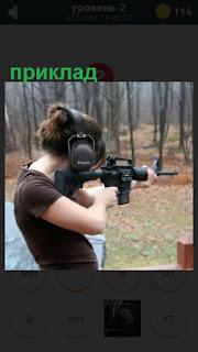 женщина стреляет по мишени приложив приклад ружья к плечу