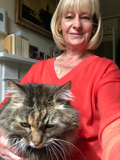 blonde woman with a tabby cat on her lap