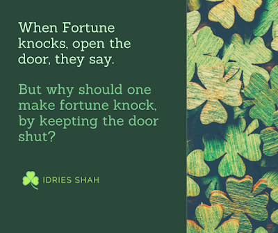 """When Fortune knocks, open the door, they say. But why should one make fortune knock, by keeping the door shut?"" A quote by Idries Shah, against a green background decorated with wooden shamrocks colored green."