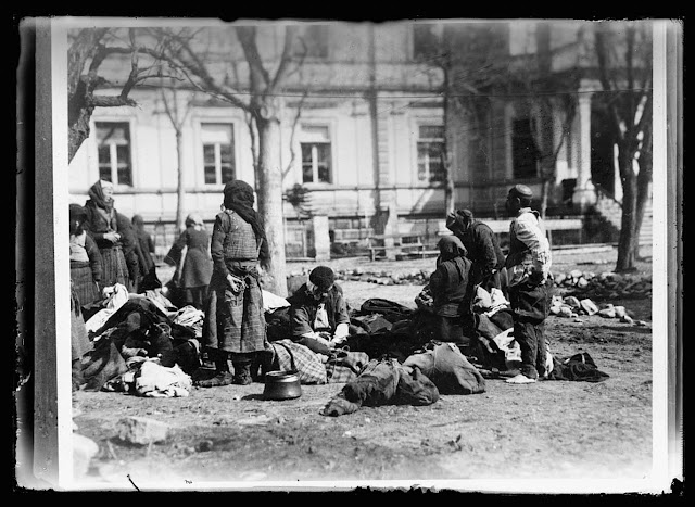 No Bath, No Food is American Rule in Balkans. A group of Balkan refugees in the yard of the American Red Cross Hospital at Monastir. To prevent the spread of Typhus and other diseases the Americans require every one asking aid of them to take a bath, which is provided in the building in the background. The food cards which they receive from the Red Cross unless the bath mark upon them has been punched. This particular group has just made its way back from an internment camp in Bulgaria. The man at the right in his bare feet has just had a bath, while the others are waiting to be called. During the bath their clothes are sterilized. The copper pot on the ground is a precious possession. It has been with this group throughout their four years of war travel