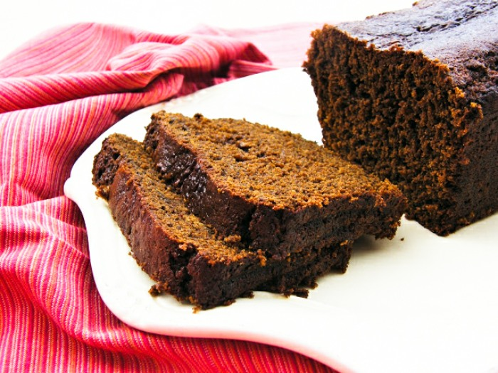 A loaf of rich Treacle Gingerbread Loaf, sliced on a white plate