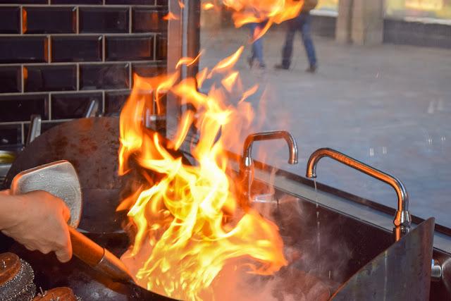 Wok To Walk Leeds, food cooking in wok with lots of flames