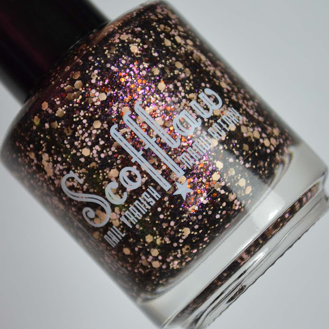 black nail polish with peach and pink glitter in a bottle