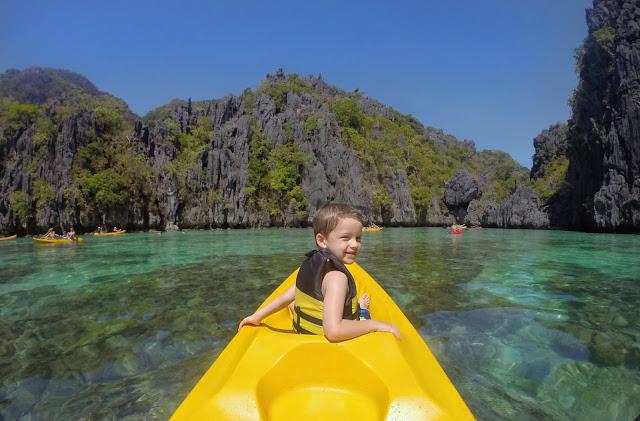 Niño en un kayak amarillo en Small Lagoon, El Nido