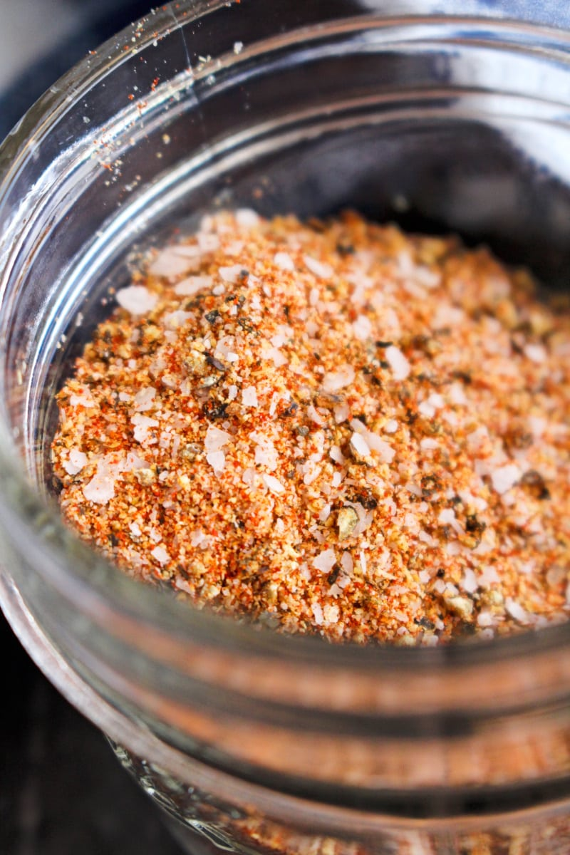Closeup side view of brisket dry rub in a small glass jar.