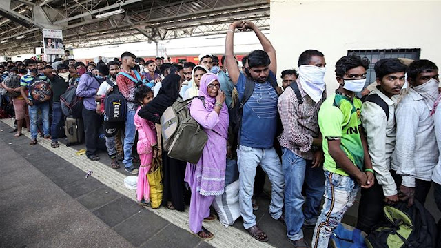 Image Attribute: Migrant workers and their families queue to board a train at Mumbai railway station after government-imposed restrictions on public gatherings in attempts to prevent the spread of COVID-19 / Source: Prashant Waydande/Reuters