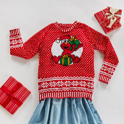Flatlay of a red festive jumper with allover colourwork and large Elmo motif