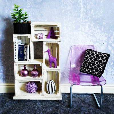 One-twelfth scale modern miniature scene containing a white shelving unit made of crates and a plastic glittery purple chair next to it. The shelving contains various decorative items in purple, white and black and the chair holds a black and white stitched cushion.