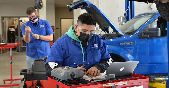 Auto student working at a computer station while another student performs maintenance on a truck