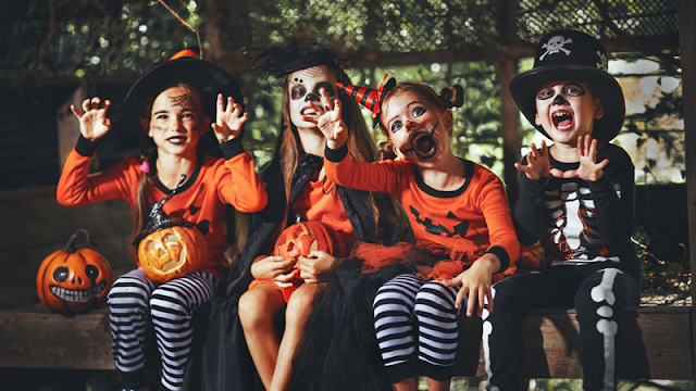 four children smiling in their Halloween costumes