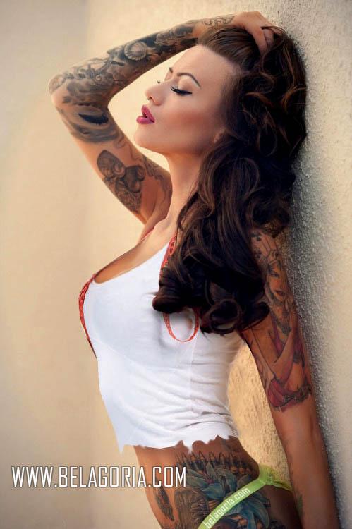 Vemos a una mujer apoyada en un muro de la calle, lleva tatuajes sexys por toda su piel