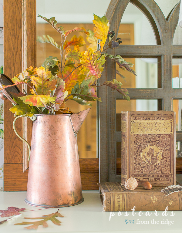 old book of poetry and copper pitcher with fall leaves