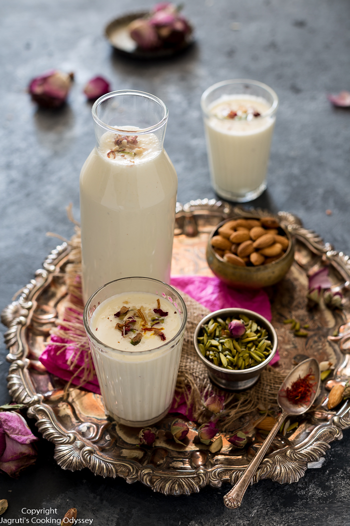 Gujarati style rich white yogurt drink, garnished with pistachio, saffron and rose petals served in a glass on silver tray.