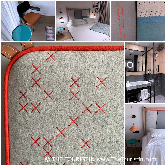Grey, red design fabric, fabric. Brown and black chair next to a teal coffee table. Grey tiled bathroom with black features.