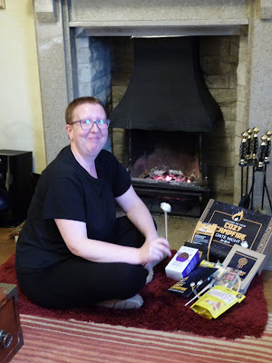 Sarah is wearing all black in front of the fire, she is smiling whilst holding a marshamallow on a stick. To her side is the Cosy Campfire box