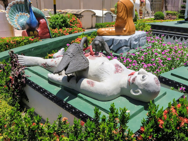 Statue of a corpse being eaten by birds at Wat Preah Prom Rath temple in Siem Reap Cambodia