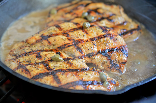 Grilled chicken piccata simmering in cast iron on a Big Green Egg kamado grill.
