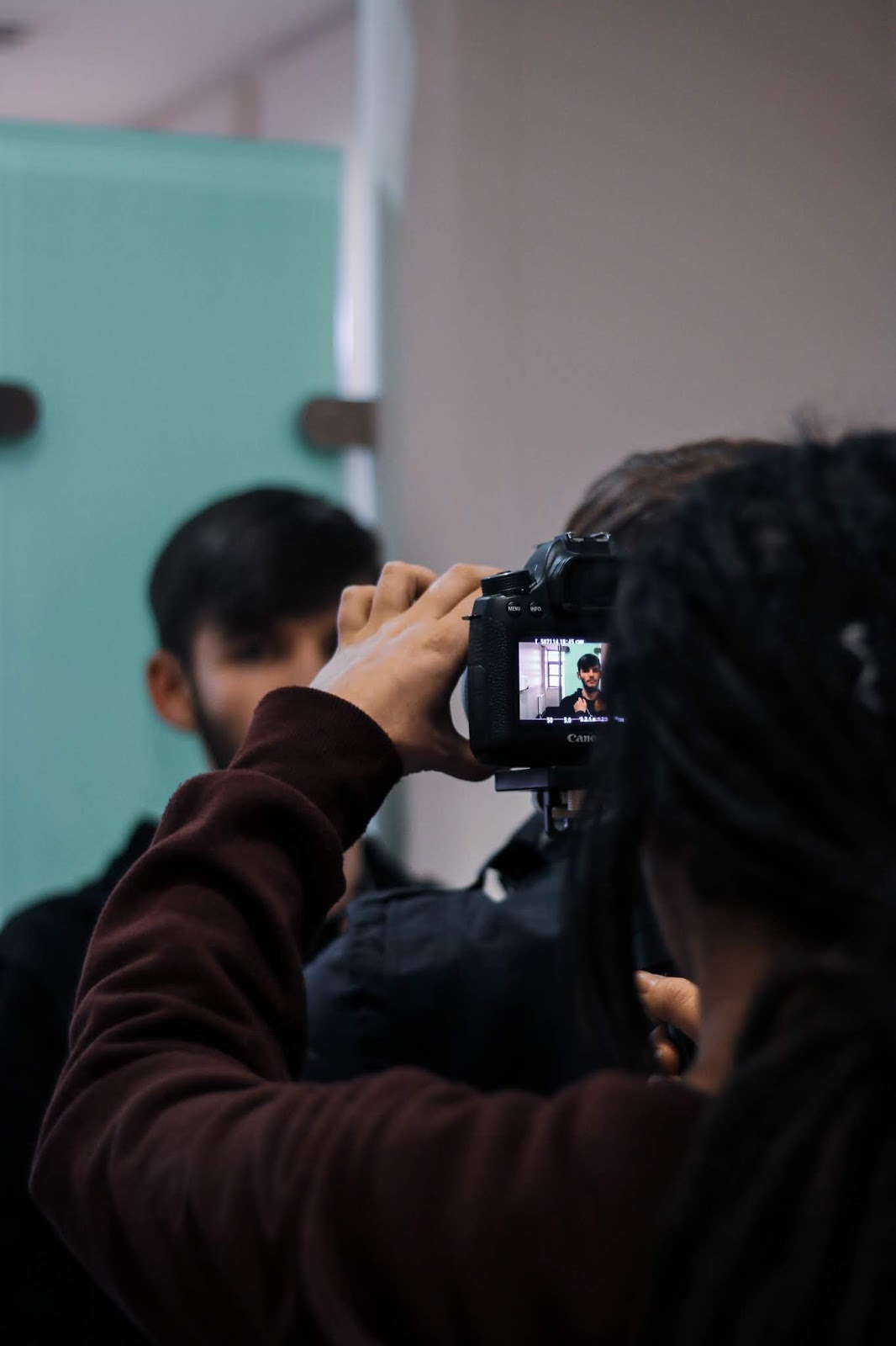 a over the shoulder photo of a girl with dreadlocks using a camera to film a boy who is in the background and blurred. The girl is wearing a Burgundy zipper and using a canon 6D camera, photo by Jordanne Lee