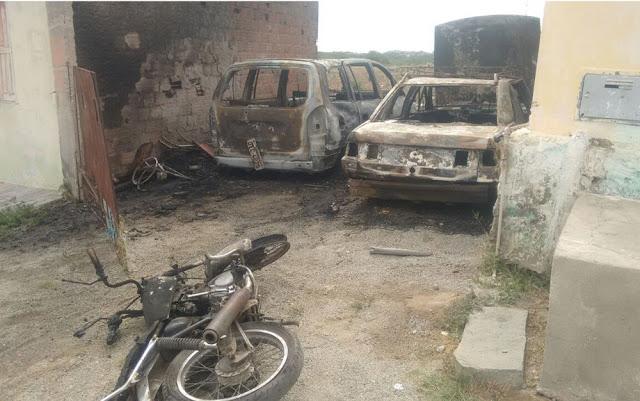 Dois carros todo queimados e uma moto no chão.