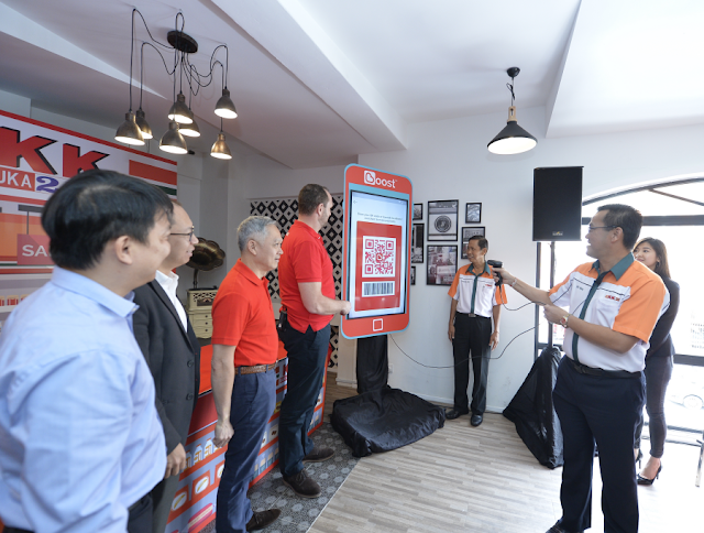 Christopher Tiffin and Datuk Seri Dr. KK Chai demonstrates how the Boost app would be used in all KK Super Mart branches