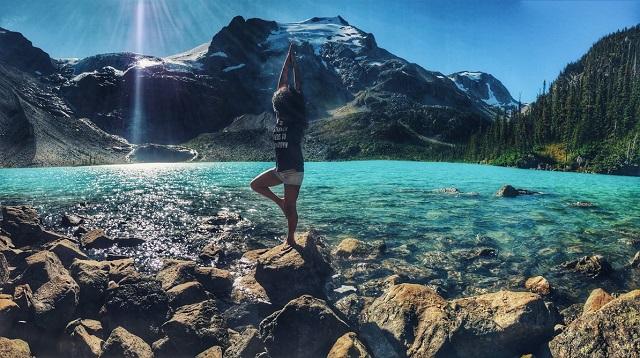 woman on rock doing sun salutation lake in canada