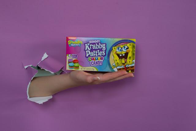 Paavo pesusieni karkkipaketti. Liila paperitausta, josta tulee käsi repeämästä.