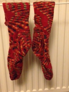 A red pair of socks hands on a drying rack