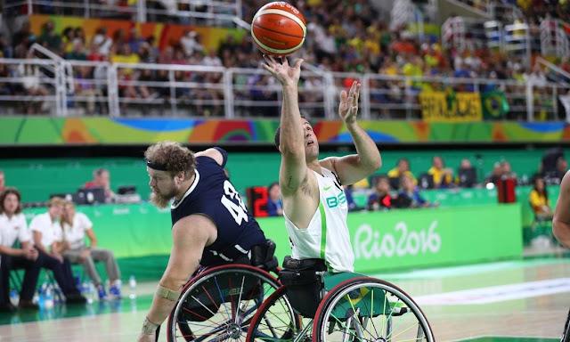 Um atleta brasileiro com uma camisa branca arremessa a bola em direção a cesta, enquanto um atleta adversário com a camisa azul escuro é driblado por ele.
