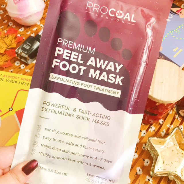 procoal premium foot mask held up above autumnal flatlay