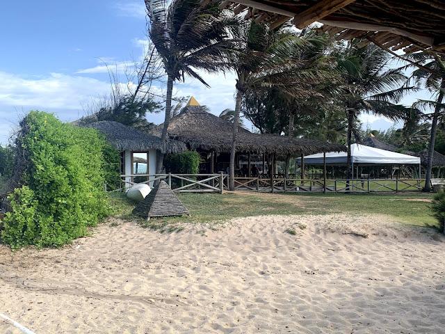 quiosque de madeira com area recreativa verde na beira da praia