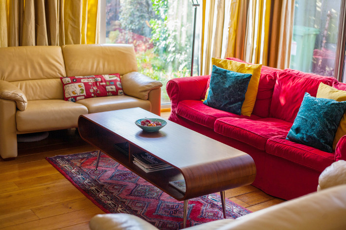 MADE hooper coffee table, red velvet couch, persian rug