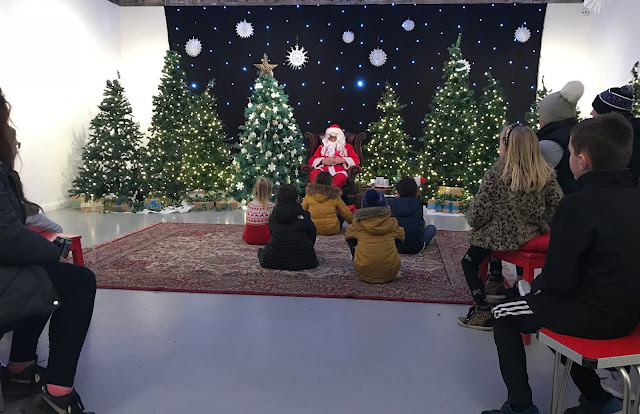Father Christmas sitting telling festive tales with lots of Christmas trees