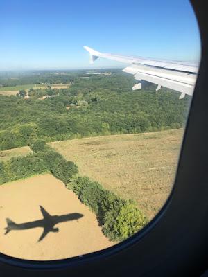 Bullauge und Flugzeug im Schatten über Landschaft
